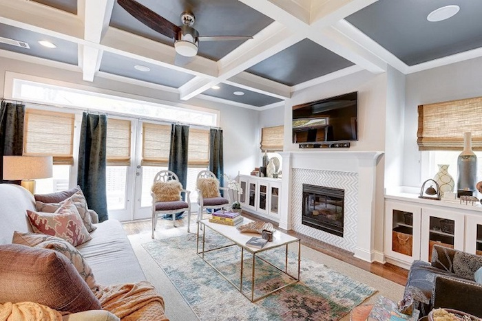 moderne einfamilienhäuser, innendesign, gemütliches zuhause mit großem sofa, viele kissen, dekos und schöner teppich, kamin, schtoren