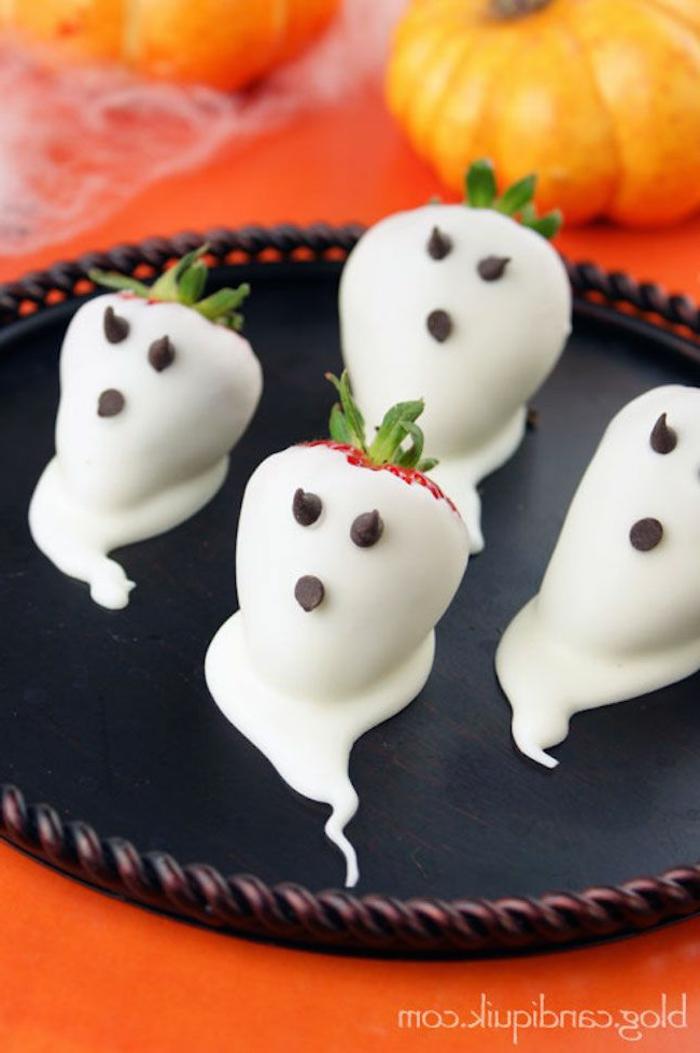 weiße Gespenster auf Erdbeeren, Schokolade Augen und Münden auf einer Platte, Halloween Essen