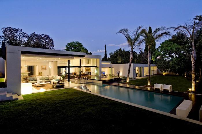 moderne häuser ideen, einstöckiges haus mit pool im garten und viele palmen, bild am späten nachmittag