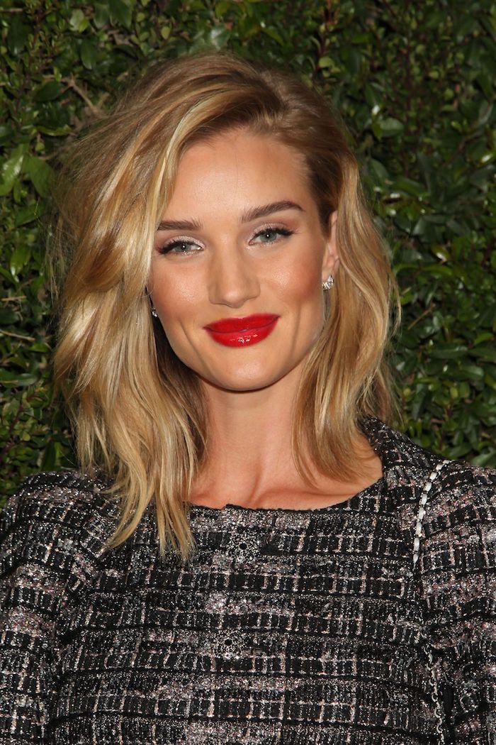 Roter Lippenstift und schwarzer Eyeliner, blonde wellige Haare mit Seitenscheitel, mittellanger Haarschnitt