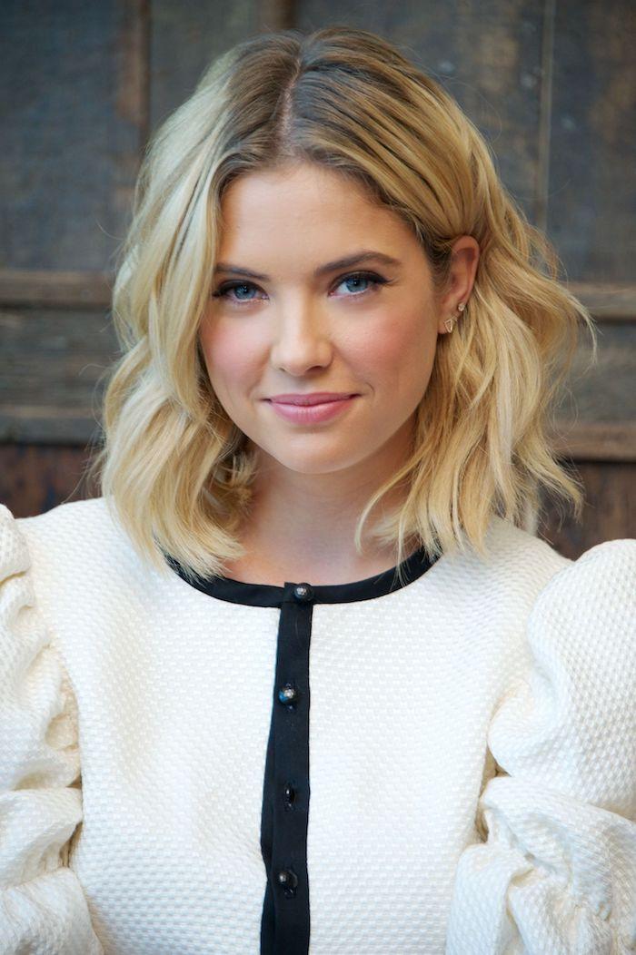 Schulterlanger Haarschnitt, blonde Haare und blaue Augen, weißer Blazer mit schwarzen Kanten