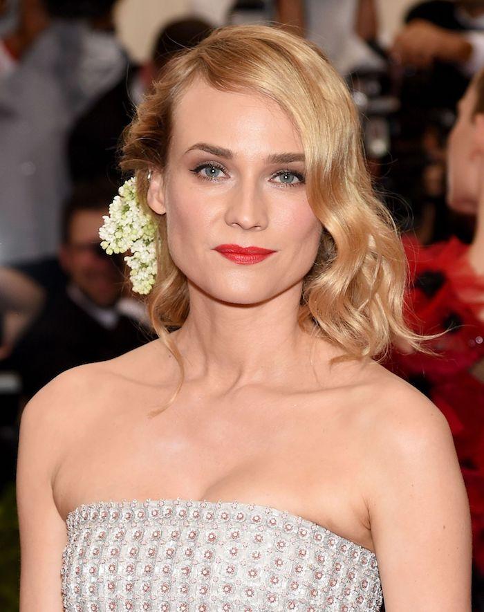Schulterlanger Haarschnitt, blonde wellige Haare mit Seitenscheitel, echte Blumen im Haar, trägerloses Kleid dekoriert mit Perlen