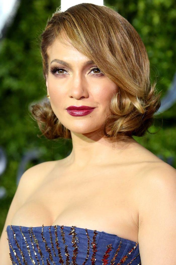 Jennifer Lopez Haarstyle, kurzer Bob mit Retro Locken, trägerloses blaues Kleid mit goldenen Pailletten, roter Lippenstift, heller Teint