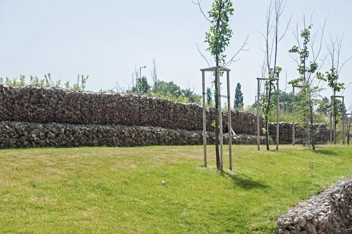 garten mit wänden aus großen grauen gabionen mit vielen grauen natursteinen, gabionen sichtschutz selber bauen, garten mit grünem rasen und bäumen