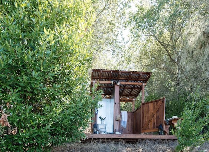 gartendusche sichtschutz selber bauen ideen, ein garten mit vielen grünen blättern und bäumen und eine gartendusche holz