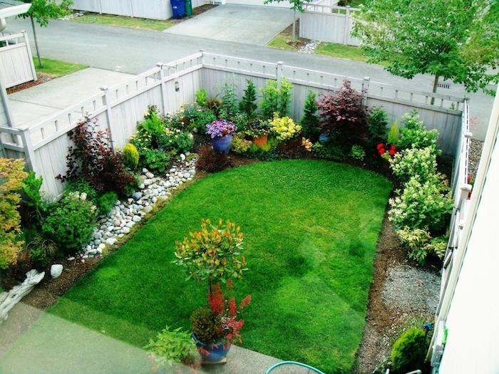 grüner rasen und ein gartenzaun aus weißem holz und sichtschutz pflanzen und grünen blumen und blättern und ein schlauch
