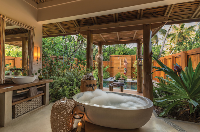 weiße badewanne im garten mit einem großen spiegel und weißen waschbecken, ein schwimmpool und eine gartendusche holz, viele pflanzen mit grünen blättern