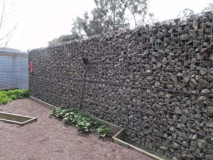 gabionen sichtschutz selber bauen, ein garten mit einer gabionenwand aus vielen kleinen grauen natursteinen, sichtschutz garten ideen