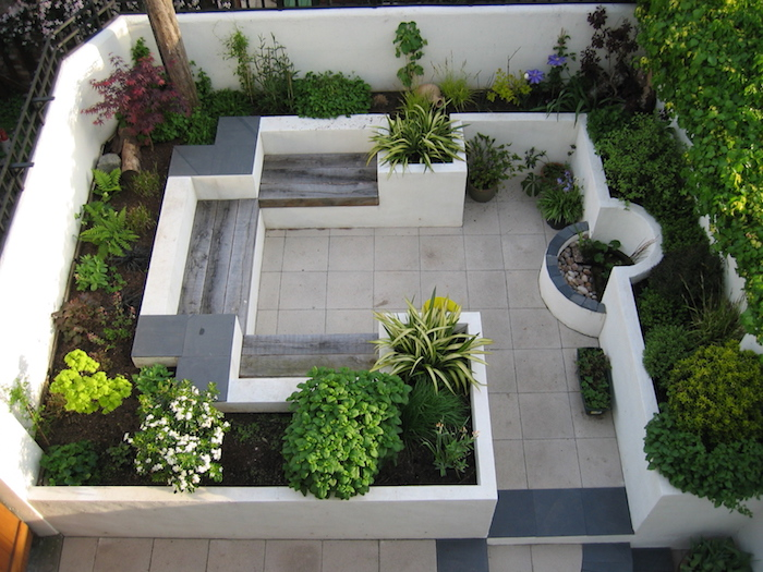 sichtschutz terrasse selber bauen, kleiner garten mit boden aus weißen und blauen fliesen und mit weißen hochbeeten mit grünen pflanzen und weißen blumen, sichtschutz pflanzen