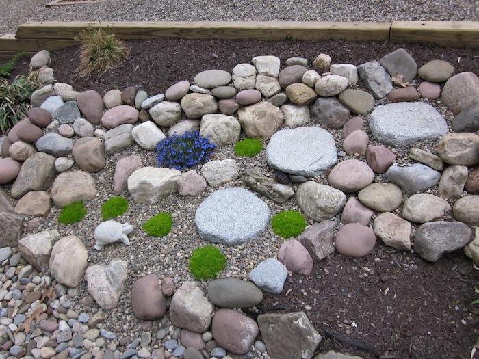 kleiner steingarten bilder, graue, weiße und beige steine für steingarten, kleine violette blumen mit grünen blättern, pflanzen für steingarten