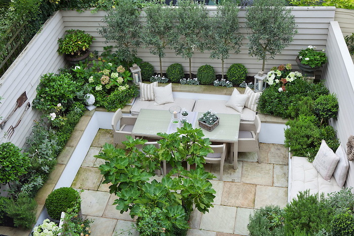 sichtschutz balkon ideen, eine terrasse mit weißen holzzaun sichtschutz und grünen bäumen und pflanzen, tisch und weiße stühle und sofas mit kissen