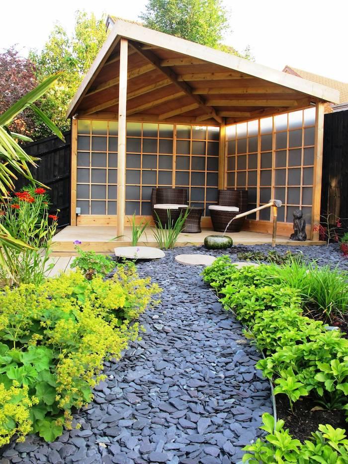 kleiner grauer gartenweg im garten mit grünen pflanzen für steingarten und mit roten blumen und brauen stühlen, gartengestaltung kleine gärten ideen