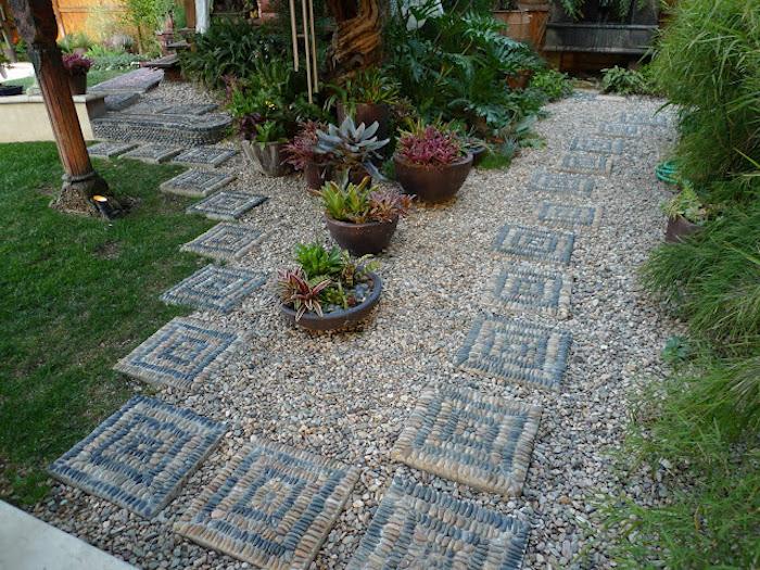 kleiner gartenweg mit vielen kleinen steinen, blumentöpfe mit grünen und roten sukkulenten pflanzen für steingarten und ein grüner rasen
