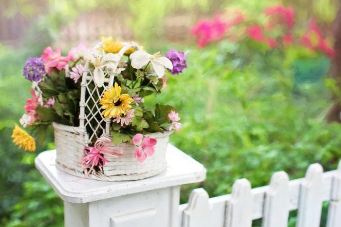 weißer Gartenzaun mit Korb als Dekoration