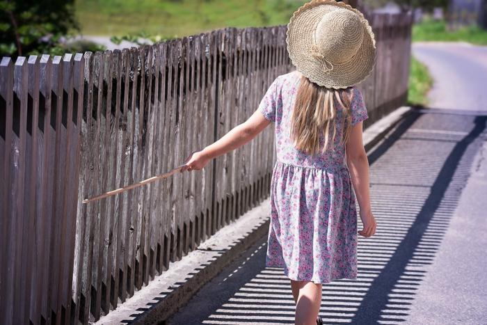 ein Mädchen spielt mit dem Zaun