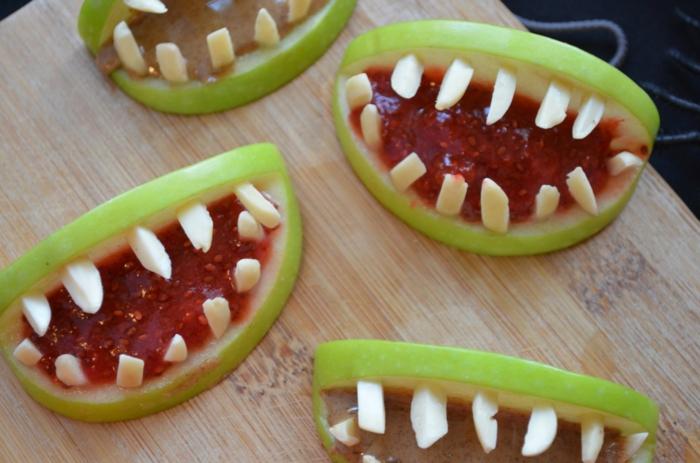 Äpfel wie Münder, mit scharfen Zähnen, rote Grütze in der Mitte, Halloween Essen