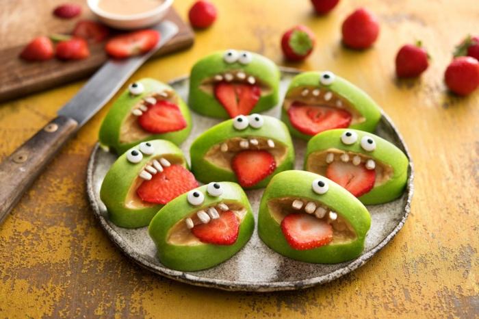 Äpfel und Erdbeeren bilden grüne Ungeheur, weiße Bonbons, weiße Augen, Halloween Essen