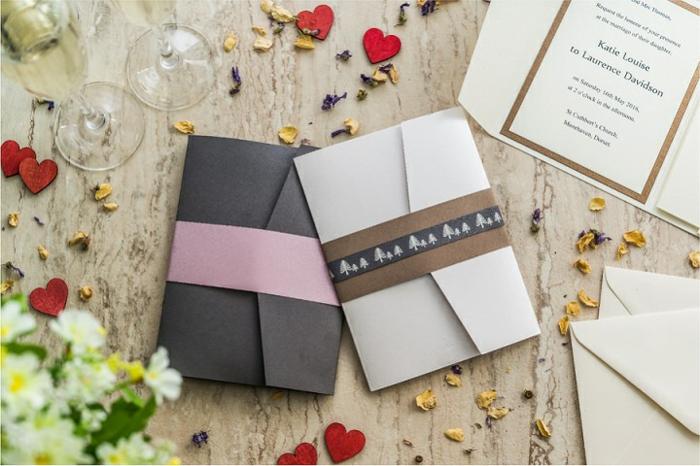 zwei Briefumschläge mit verschiedenen Dekoration, zwei hohe Weingläser und Herzen als Hochzeitsdeko