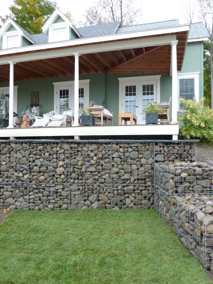 sichtschutz terrasse selber bauen, ein haus mit garten mit gabionen sichtschutz aus grauen kleinen steinen und mit einem grünen rasen