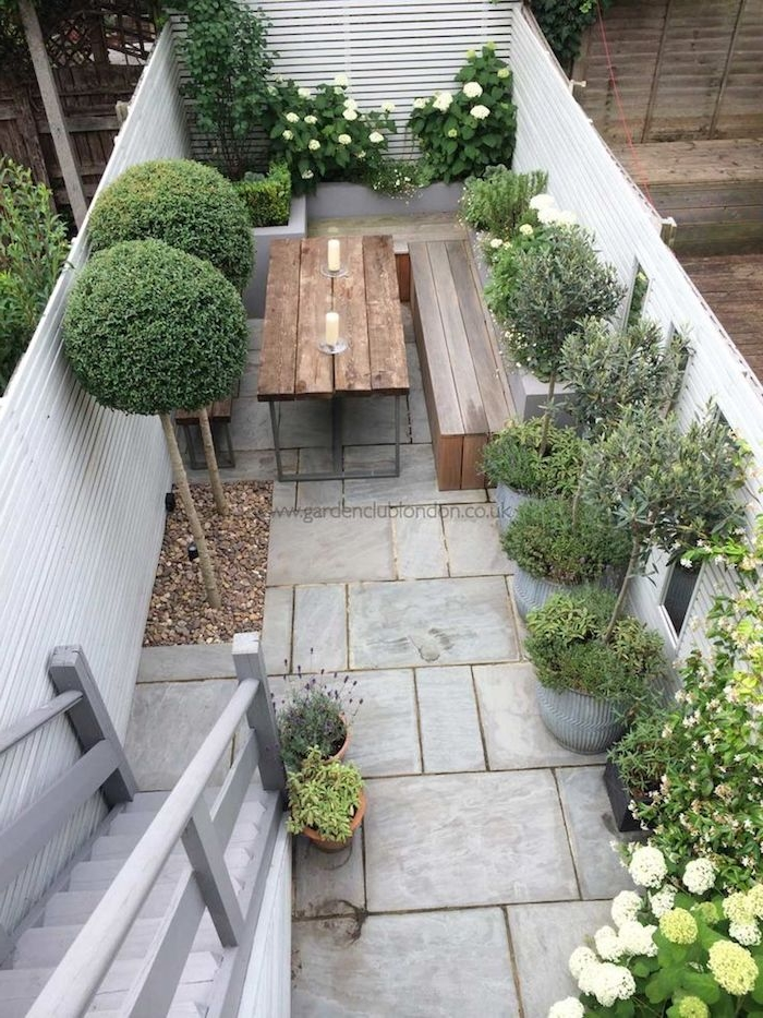 weißer zaun sichtschutz aus holz und tisch und bank aus holz, pflanzen als sichtschutz und eine graue treppe, sichtschutz terrasse selber bauen