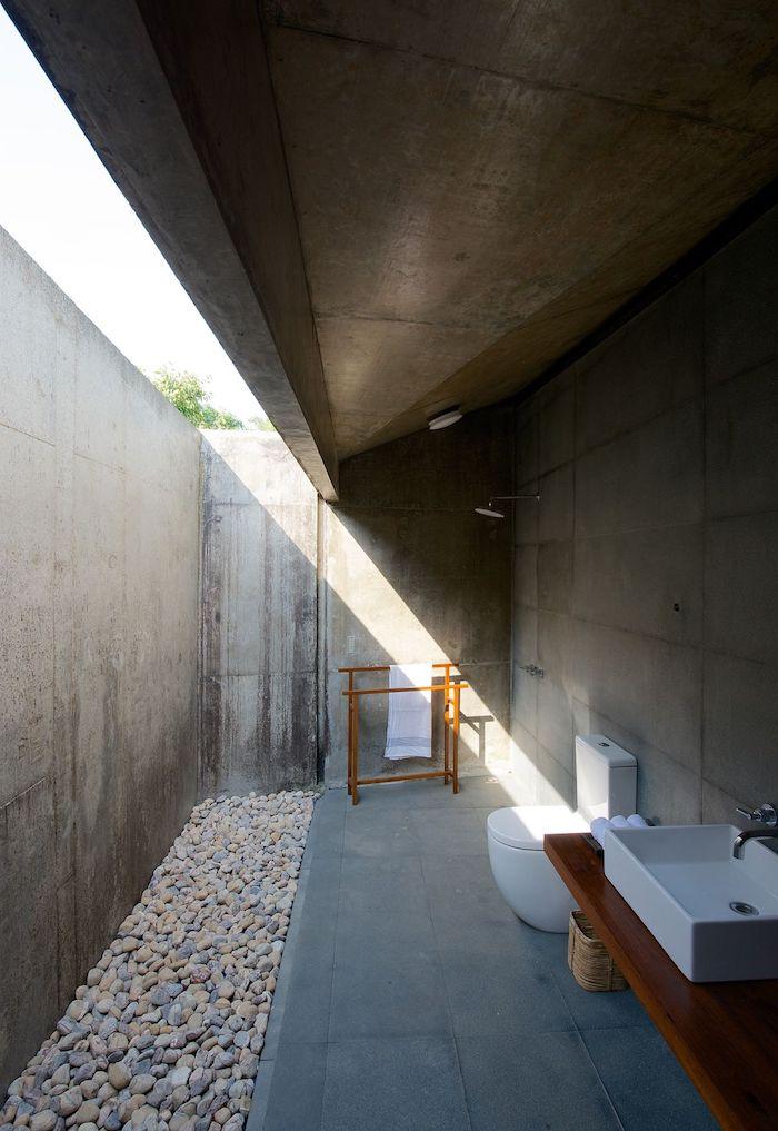 ein haus mit terrasse mit grauen wänden und einer outdoor dusche, weißen waschbecken und einem boden aus vielen kleinen steinen