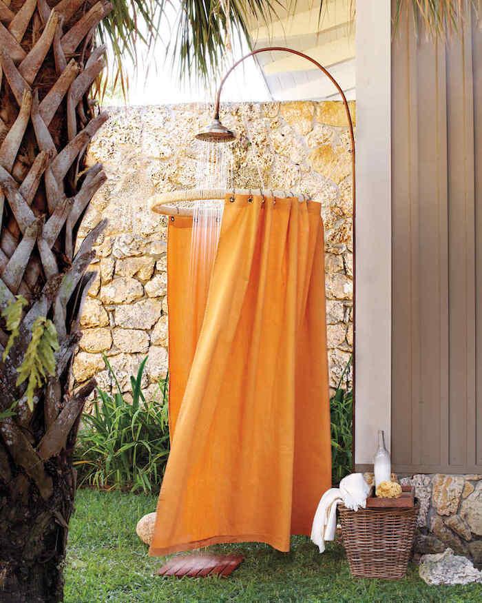 grüner rasen in einem garten mit großer palme mit grünen blättern und einer gartendusche mit einem orangen sichtschutz, solar gartendusche bauen ideen