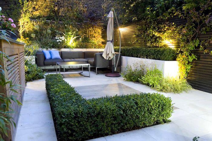 zaun sichtschutz holz, ein zaun mit vielen grünen kletterpflanzen und eine grüne hecke, ein großer beiger sonnenschirm im garten mitgrauen sofas mit grauen und blauen kissen