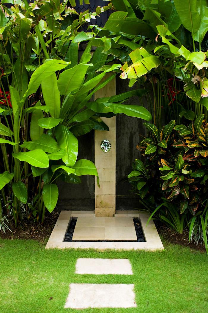 garten mit einem grünen rasen und einem gartenweg aus weißen fliesen, garten mit einer dusche und sichtschutz aus vielen grünen pflanzen