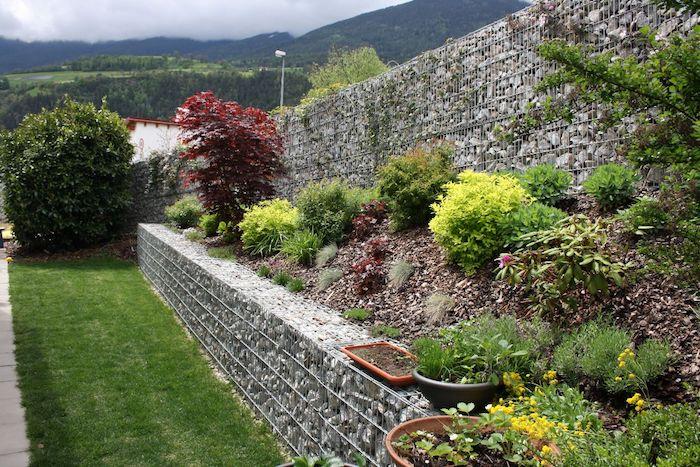kleiner garten mit einem grauen gabionen sichtschutz mit vielen grauen natursteinen und mit kleinen grünen pflanzen, gabionen selber bauen