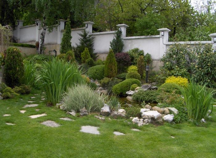 ein weißer gartenzaun und kleiner grüner garten mit weißen steinen und gelben und grünen pflanzen und ein grüner rasen