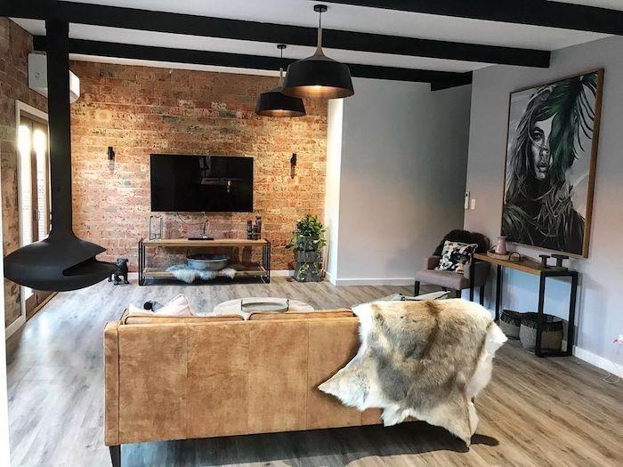 schönes haus, insider look, großes stilvolles wandbild in schwarz und weiß, fell deko, sofa, kaminofen, steinwand