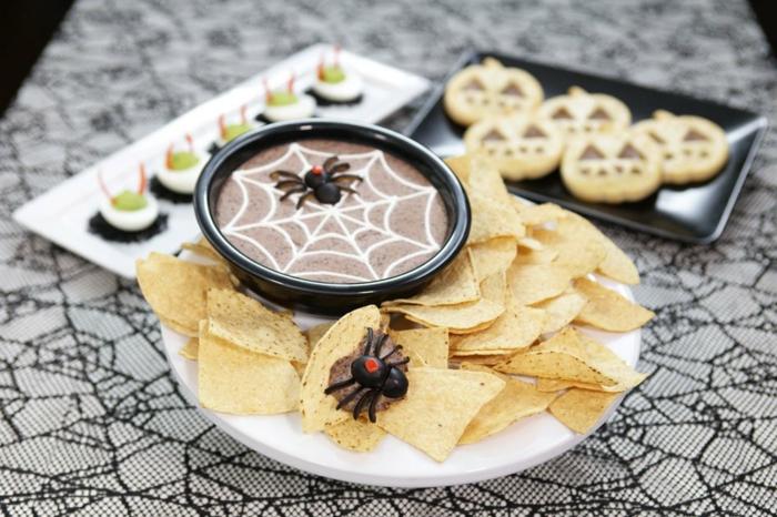 eine Soße in brauner Farbe mit einem bemalten Spinnennetz, Nachos, Halloween Essen