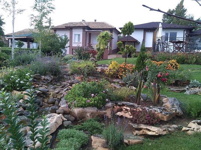 drei häuser und ein kleiner steingarten mit gartenteich mit grauen und braunen steinen und orangen und violetten blumen, ein baum mit grünen blättern, steingarten anlegen