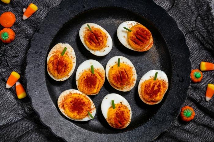 Halloween Buffet, gekochte halbe Eier mit Paprika bestreut, wie kleine Kürbisse