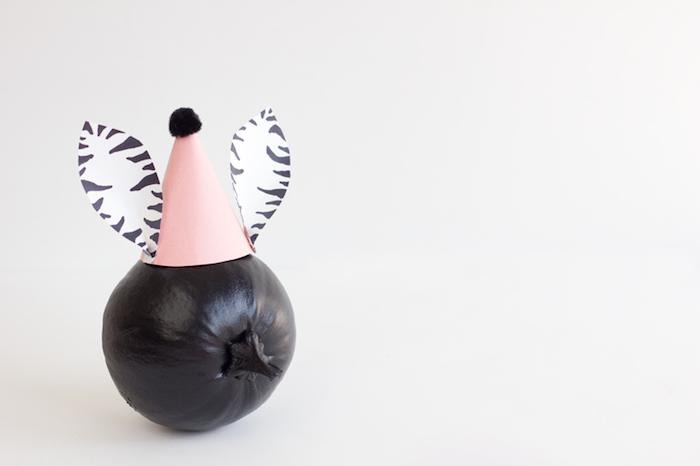 Kürbis mit schwarzer Acrylfarbe bemalen, Partyhütchen mit Ohren aus Papier basteln