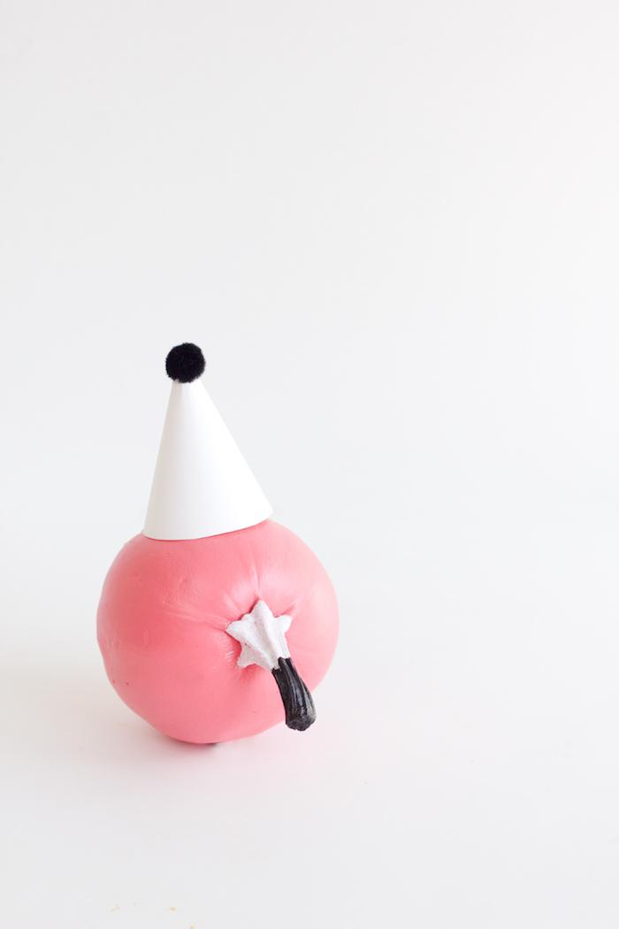 Bemalter Kürbis mit Partyhütchen aus Papier und Pompon, schöne Deko Idee für Kinderparty