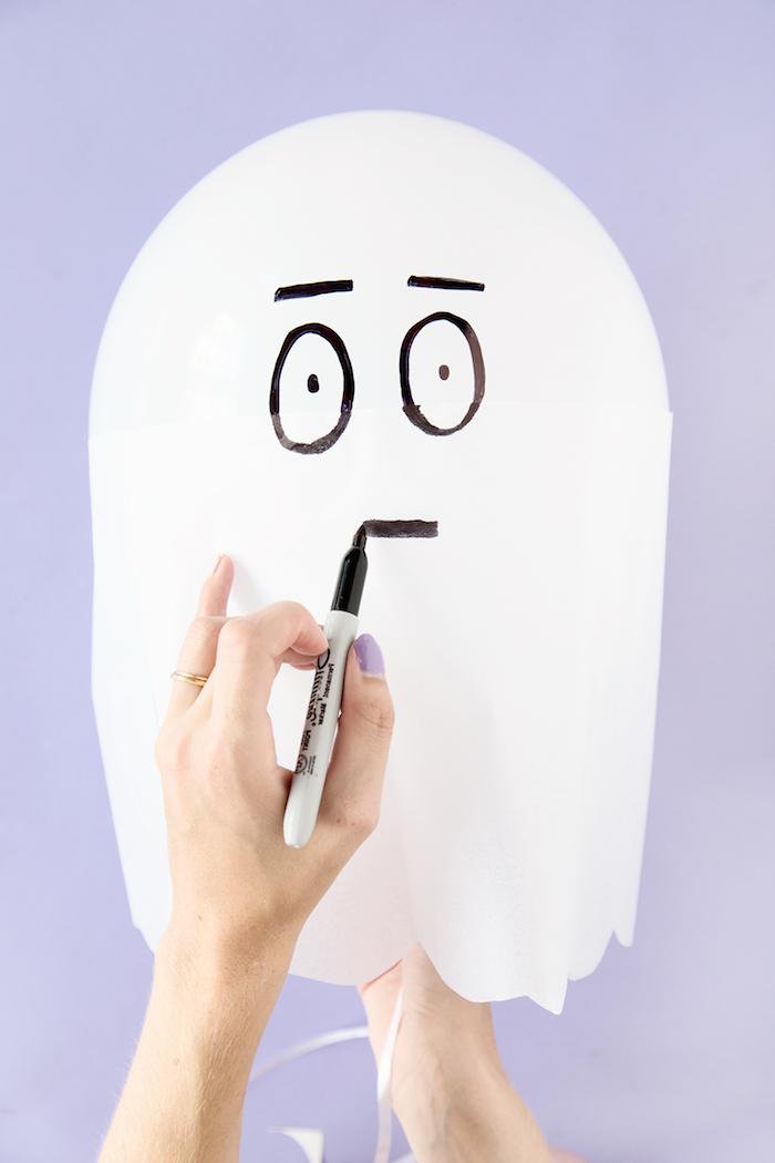Gespenst aus weißem Ballon und Papier selber machen, Gesicht mit schwarzem Marker zeichnen