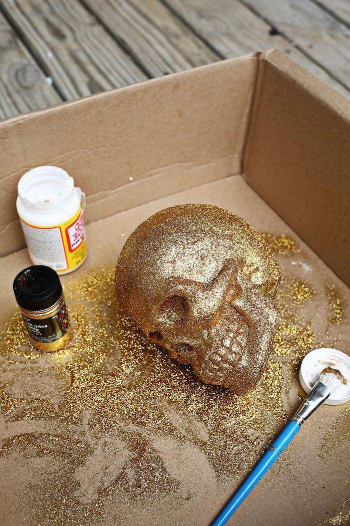 Deko Schädel mit goldenem Glitter besprühen, gruselige Deko Ideen zu Halloween zum Nachmachen