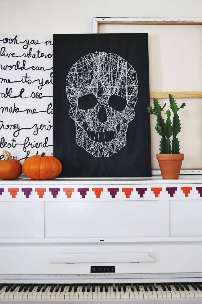 halloween deko basteln, bild mit schädel aus weißem faden, kleine kürbisse, schrank mit enthnischen motiven