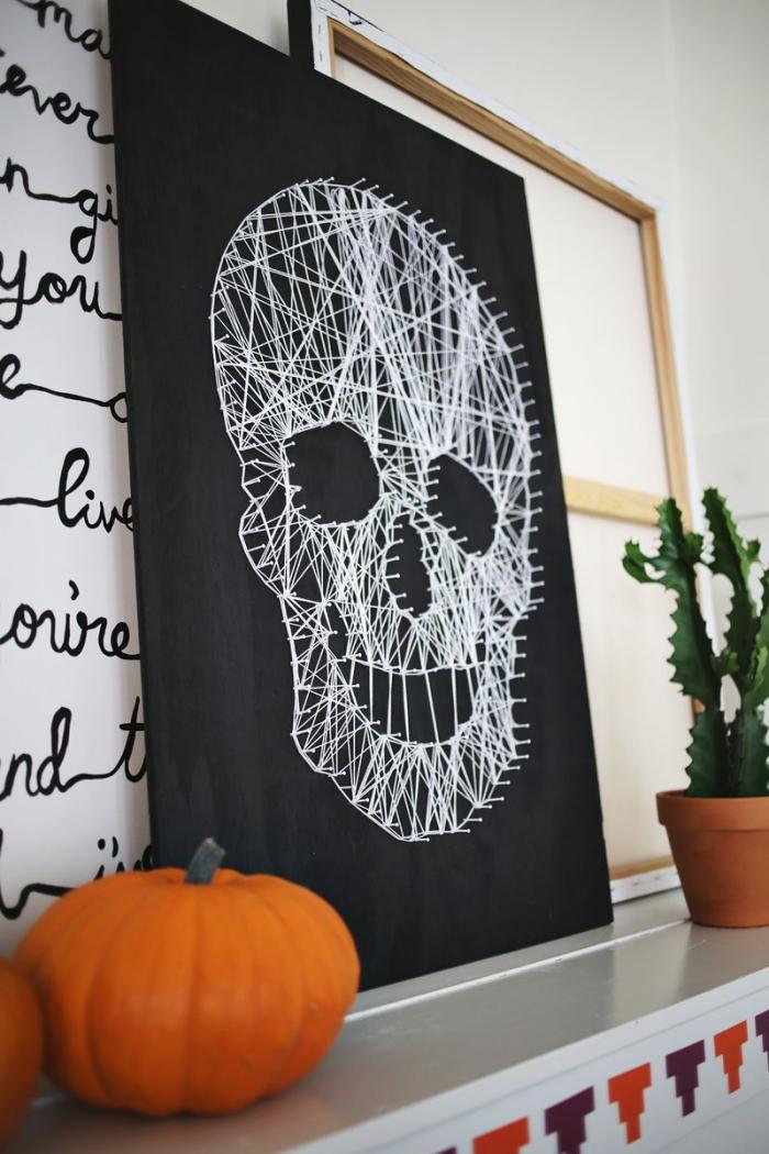 halloween deko basteln, großes bild mit schädel aus weißem faden, kürbisse