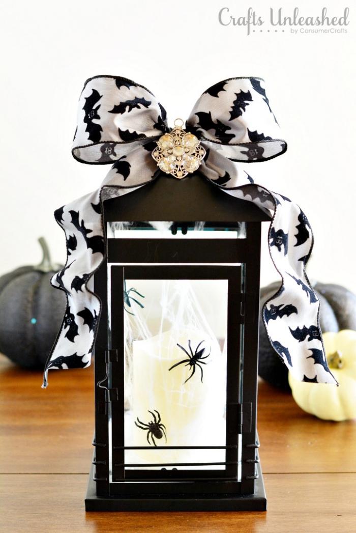 halloween deko für draußen, schwarze laterne, weiße kerze, kleinen spinnen, große schleife