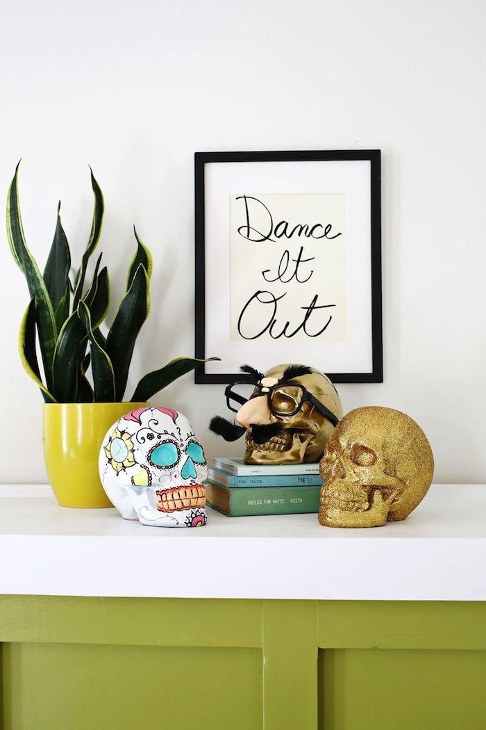 Das Wohnzimmer zu Halloween dekorieren, drei gruselige Deko Schädel in verschiedenen Farben