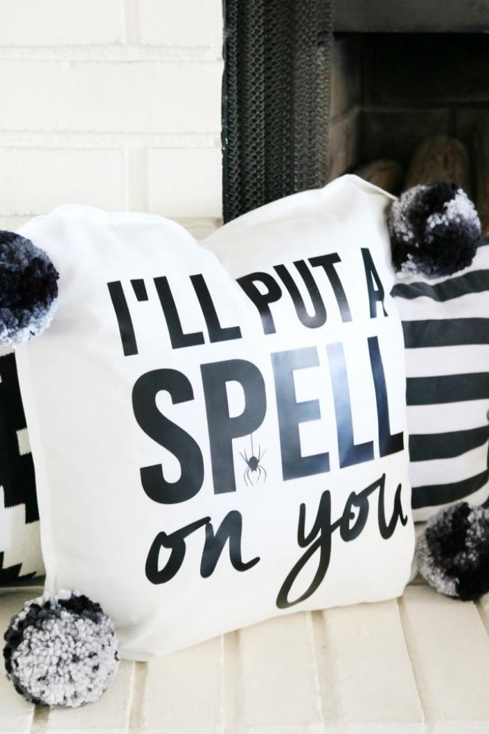 halloween deko ideen, weißer kussenbezug mit bommeln dekoriert mit schwarzen buchstaben, schriftzug