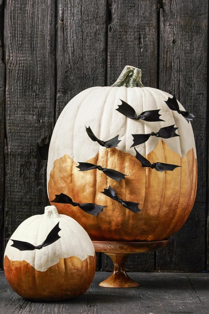 Halloween Kürbis kreativ bemalen und dekorieren, mit weißer und goldener Farbe, schwarze Schleifen als Fledermäuse