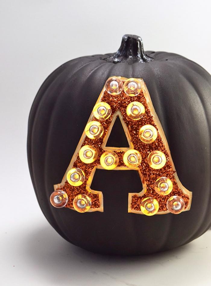 halloween deko selber machen, schwarzer kürbis aus kunststoff, große buchstabe, laterne