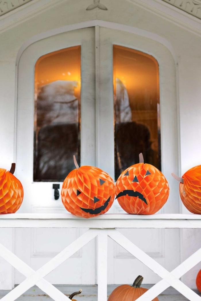 wabenbälle aus papier, halloween ideen, diy deko basteln, orangenfarbene bälle aus papeir mit augen und munden