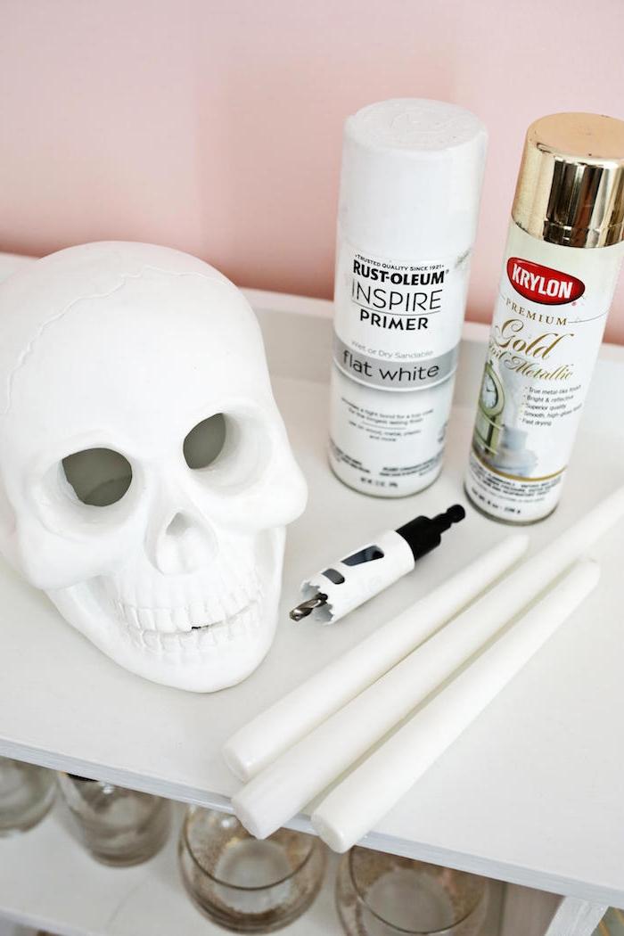 Kerzenhalter aus Deko Schädel selber machen, mit goldenem Spray besprühen, gruselige Halloween Deko Ideen
