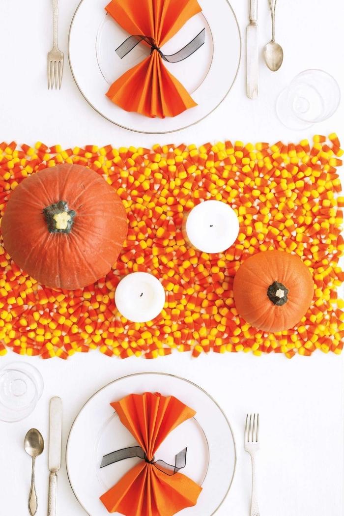 halloween ideen, tischdeko selber machen, tischläuder aus bonbons, weiße kerzen, orangenfarbene servietten