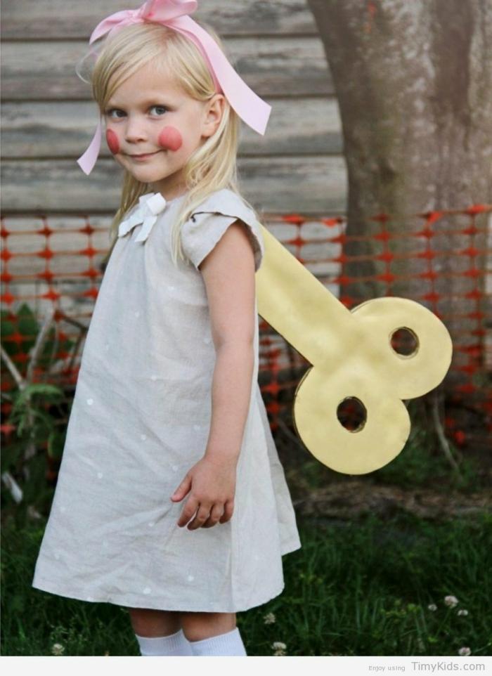eine kleine Puppe mit grauem Kleid, ein Schlüssel an dem Rücken, eine rosa Schleife und rote Wange, Kinderkostüme selber machen