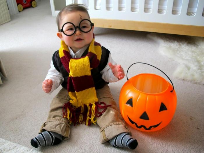 ein kleines Baby wie Harry Potter maskiert mit dem entsprechenden Schal, Brillen und Narben